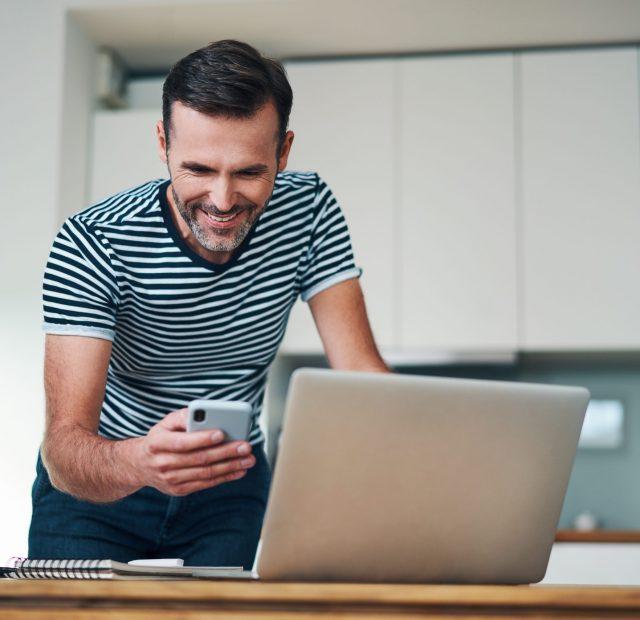 Lachender Mann mit Handy und Laptop